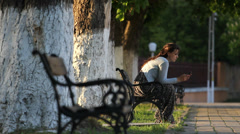 Beautiful young lady talk on the phone, laught in nature, sit on bench in parck Stock Footage