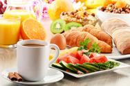 Stock Photo of breakfast with coffee, orange juice, croissant, egg, vegetables