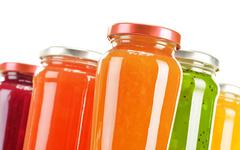 Jars of fruity jams on kitchen table. preserved fruits Stock Photos