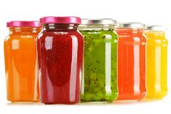 jars of fruity jams on kitchen table. preserved fruits - stock photo