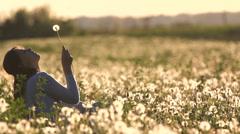 Beautiful lady blow a dandelion at sunset, in dandelion field in bloom Stock Footage