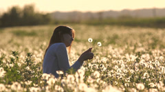 Beautiful young lady play with two dandelion, flourish dandelion field at sunset Stock Footage
