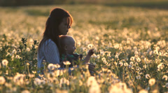 Gentle touch, young mother hold her baby play with dandelion flower in field - stock footage