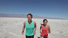 Running athletes couple in desert trail run Stock Footage