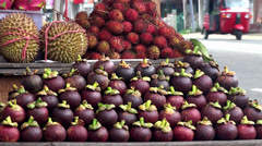 Ripe purple mangosteens at a street market - stock footage