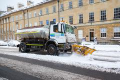 snow plough clears street in bath, uk - stock photo