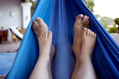 spain, mid adult man and boy legs relaxing on hammock - stock photo