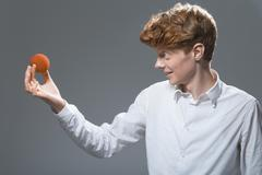 Young man holding and looking at ball, smiling Stock Photos