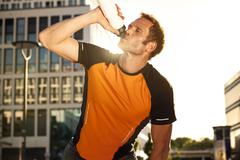 athletic man outdoors drinking from bottle - stock photo