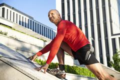 Stock Photo of mature athletic man stretching outdoors