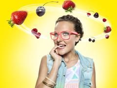 young woman looking at flying fruit, composite - stock photo