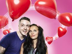 couple looking at heart-shaped balloons, composite - stock photo
