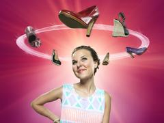Stock Photo of smiling young woman looking at flying shoes, composite