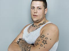 portrait of young man with tattoos, close up - stock photo