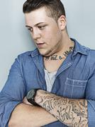 Portrait of young man with tattoo, close up Stock Photos