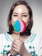 Stock Photo of portrait of young woman holding lollipop, close up