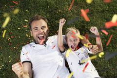Germany, father and son lying on lawn, wearing football shirts, cheering Stock Photos