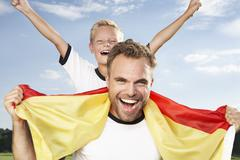 Germany, cologne, father and son cheering in football outfit Stock Photos