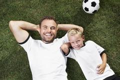 germany, father and sun lying on lawn, wearing football shirts - stock photo