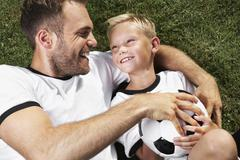 Germany, father and sun lying on lawn, wearing football shirts Stock Photos