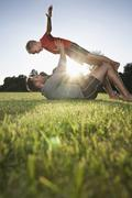 Germany, cologne, father holding son aloft on soccer field Stock Photos