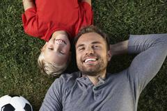 Germany, cologne, father and son lying in meadow Stock Photos