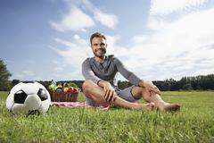 Germany, cologne, man sitting on blanket with picnic basket an d soccer ball Stock Photos