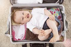 germany, north rhine westphalia, cologne, baby girl lying in briefcase, smili - stock photo