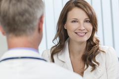 happy woman patient meeting with male doctor in office - stock photo
