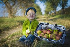 Germany, saxony, boy sitting with basket full of apples, smiling Stock Photos