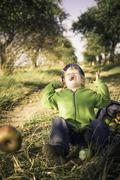 Germany, saxony, boy sitting with basket full of apples, laughing Stock Photos