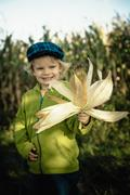 Germany, saxony, boy holding corn cob, smiling Stock Photos