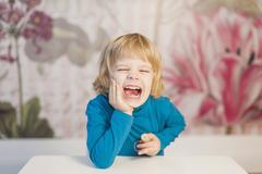 germany, saxony, boy sitting at table, smiling - stock photo