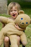 Germany, baden wuerttemberg, portrait of girl playing with teddy bear, smilin Stock Photos