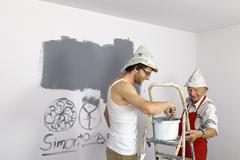 Stock Photo of germany, grandfather and grandson painting wall