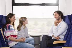 Germany, brandenburg, family traveling in train, smiling Stock Photos