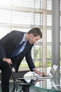 germany, hannover, businessman using laptop on conference table - stock photo