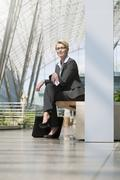germany, hannover, portrait of businesswoman sitting on bench, smiling - stock photo