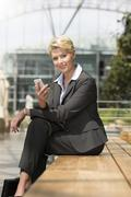 germany, hannover, portrait of businesswoman sitting on bench with smart phon - stock photo