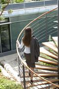 businesswoman on spiral staircase - stock photo