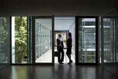 Stock Photo of two businesswomen talking in office building