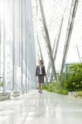 Businesswoman walking in modern courtyard Stock Photos