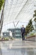businessman walking in courtyard - stock photo
