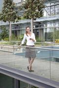 Businesswoman with cell phone on footbridge Stock Photos