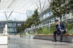 Businessman with cell phone in courtyard Stock Photos