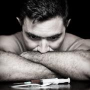 Depressed drug addict and a syringe Stock Photos