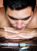 Addict with the cravings looking at drugs Stock Photos