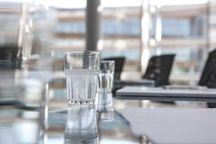glasses of water on conference room table - stock photo