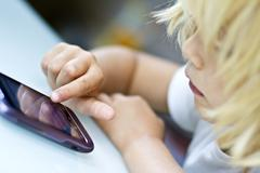 germany, kiel, girl playing with smart phone, close up - stock photo