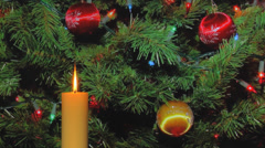 Golden holiday candle with holiday decorations in background Stock Footage